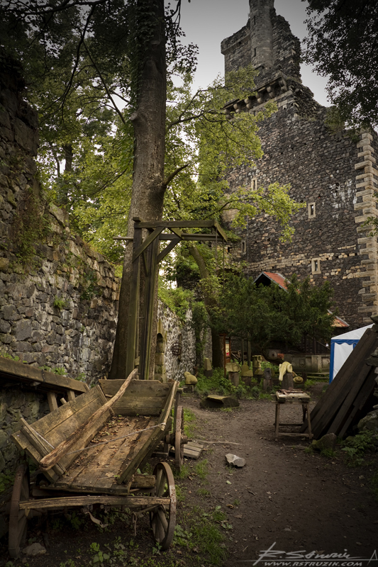 Zamek Grodziec. Eksponaty zebrane na dziedzińcu przy szczątkach południowo-wschodniego muru. W tle rzeczony taras poniżej szczytu wieży.